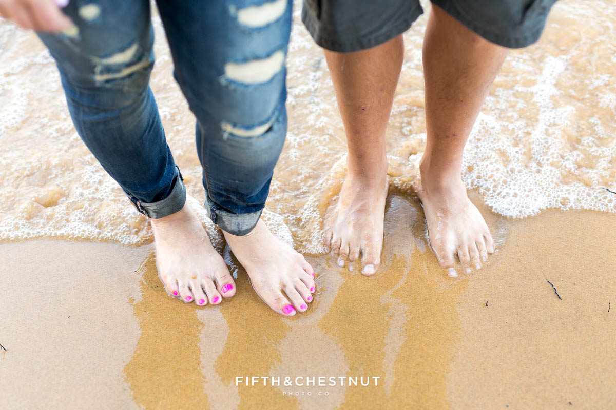 feet in the sand with water rushing up behind them for a summer Tahoe engagement