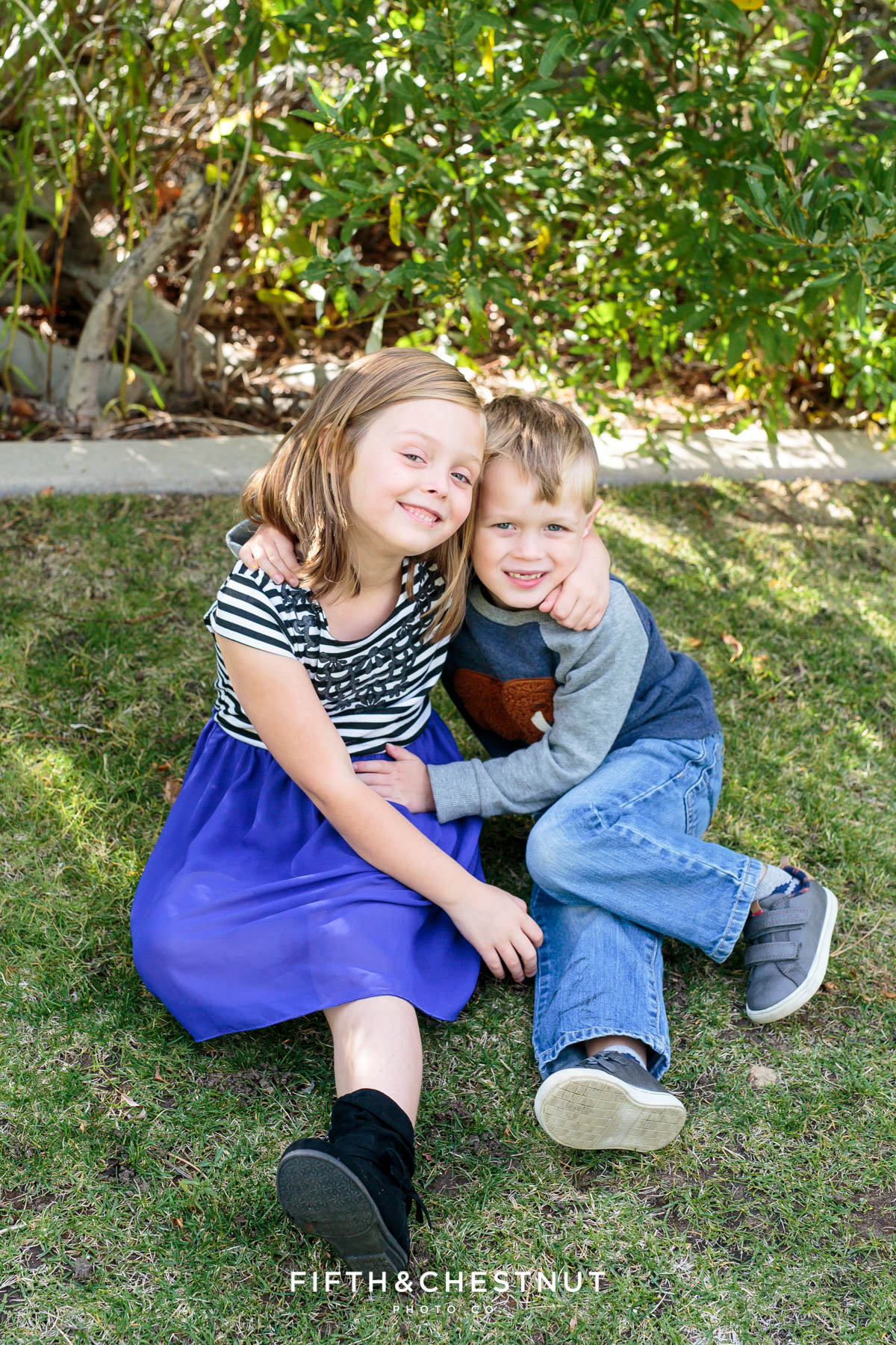 a boy and girl sitting on grass wearing blue pose for Bartley Ranch Portraits by Reno Family Photographer
