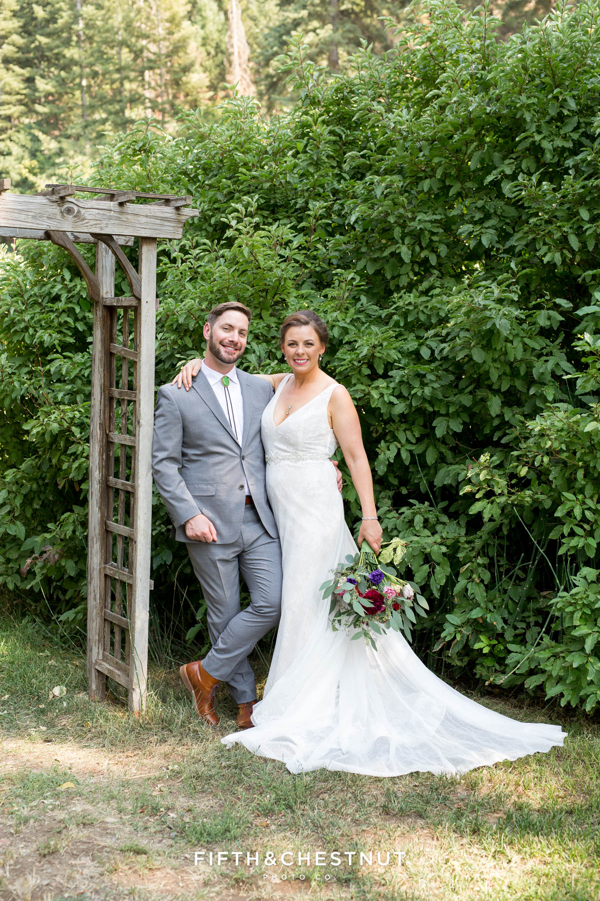 bride and groom stand near an old arbor for Greenhorn Creek Guest Ranch Wedding portraits