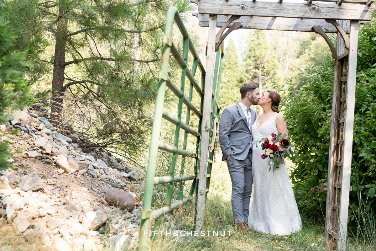 bride and groom kiss under arbor at a bright and summery wedding bouquet for a Greenhorn Creek Guest Ranch Wedding