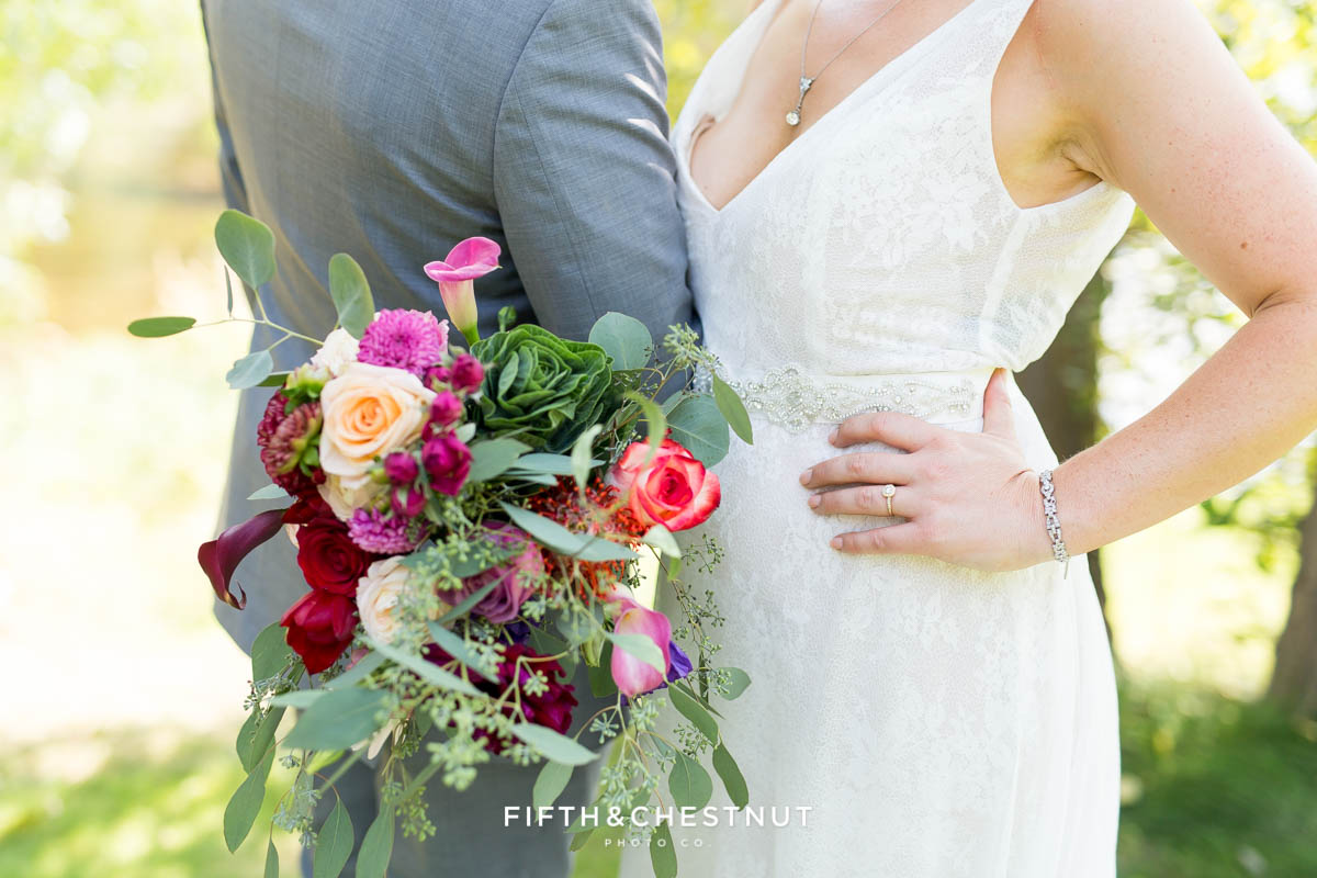 up close shot of bride with hand on hip, holding her bouquet alongside her groom wearing a gray suit for their bright and summery wedding bouquet for a Greenhorn Creek Guest Ranch Wedding