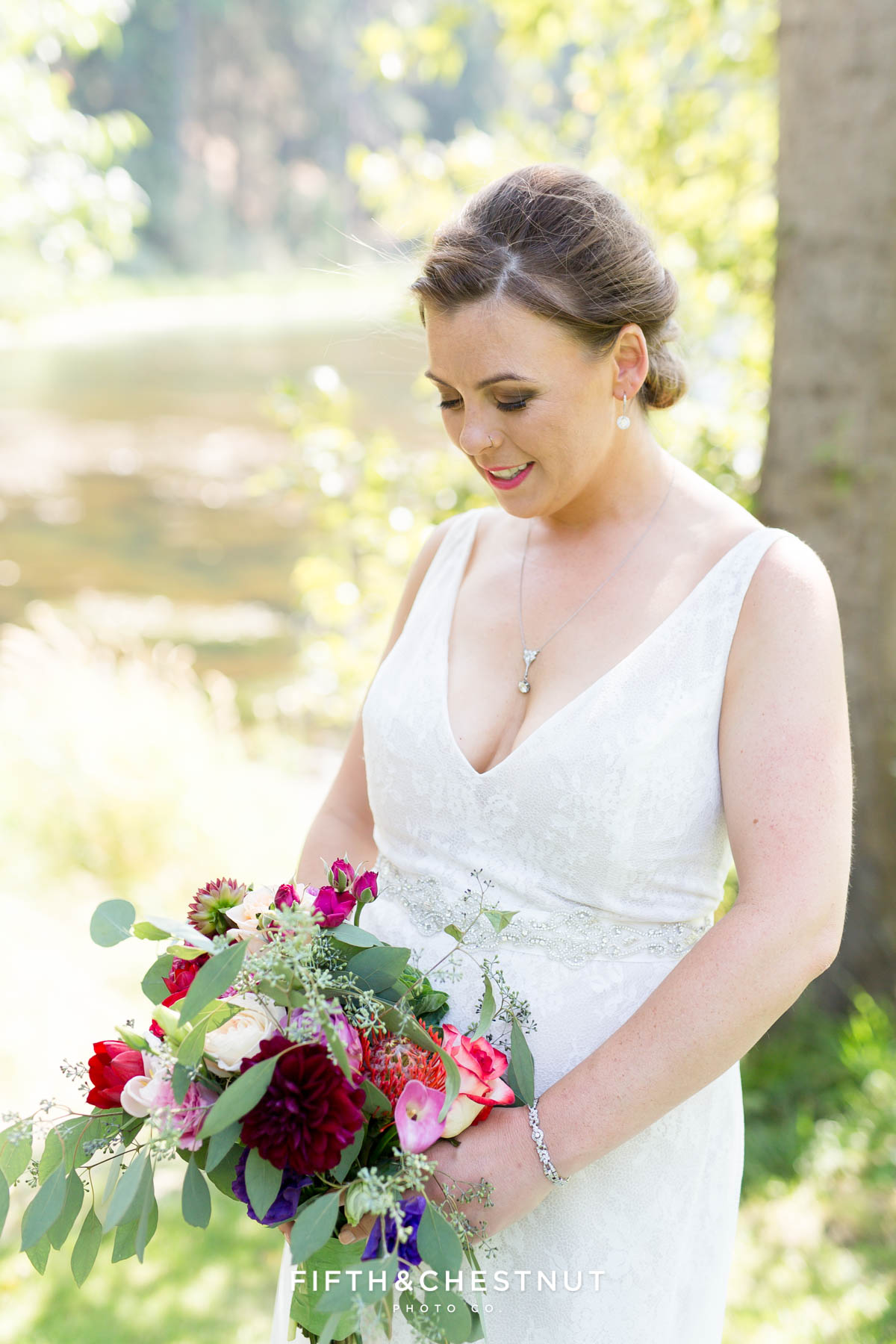 bride looks down at her wedding flowers while wearing a lacy white wedding dress