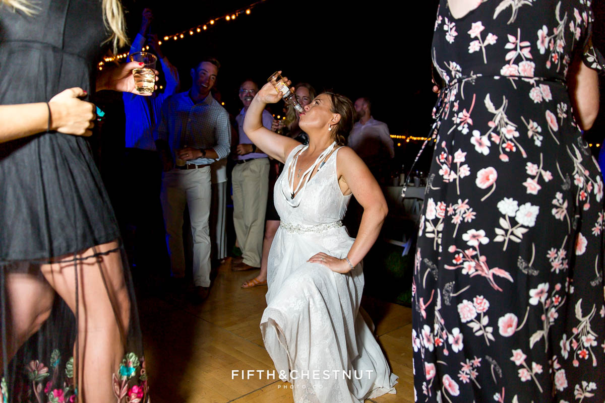 bride chugs a smirnoff ice at her Greenhorn Creek Guest Ranch Wedding