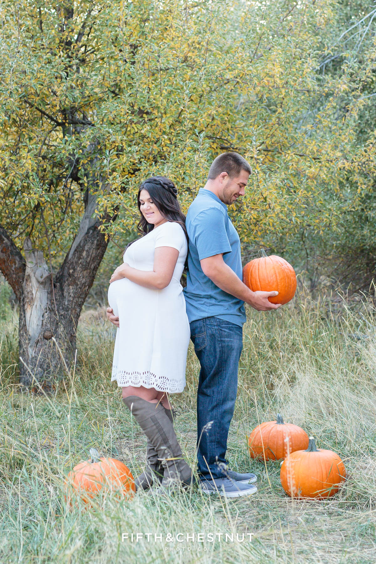 Close up of Husband and his pregnant wife stand back to back in an apple orchard surrounded by pumpkins while he looks down at a pumpkin he's holding and she looks down at her baby bump for their fall maternity portraits