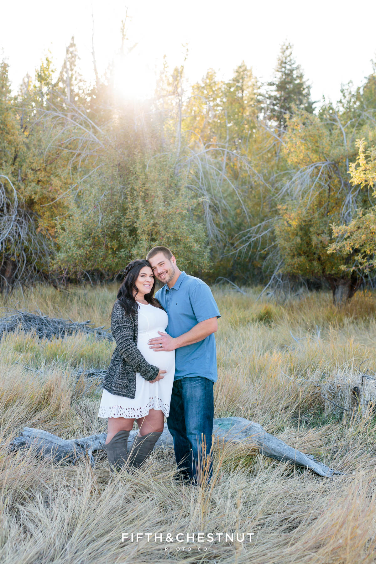 Expecting couple snuggles together as the sun sets over a rustic apple orchard for their fall maternity portraits by Reno Maternity Photographer