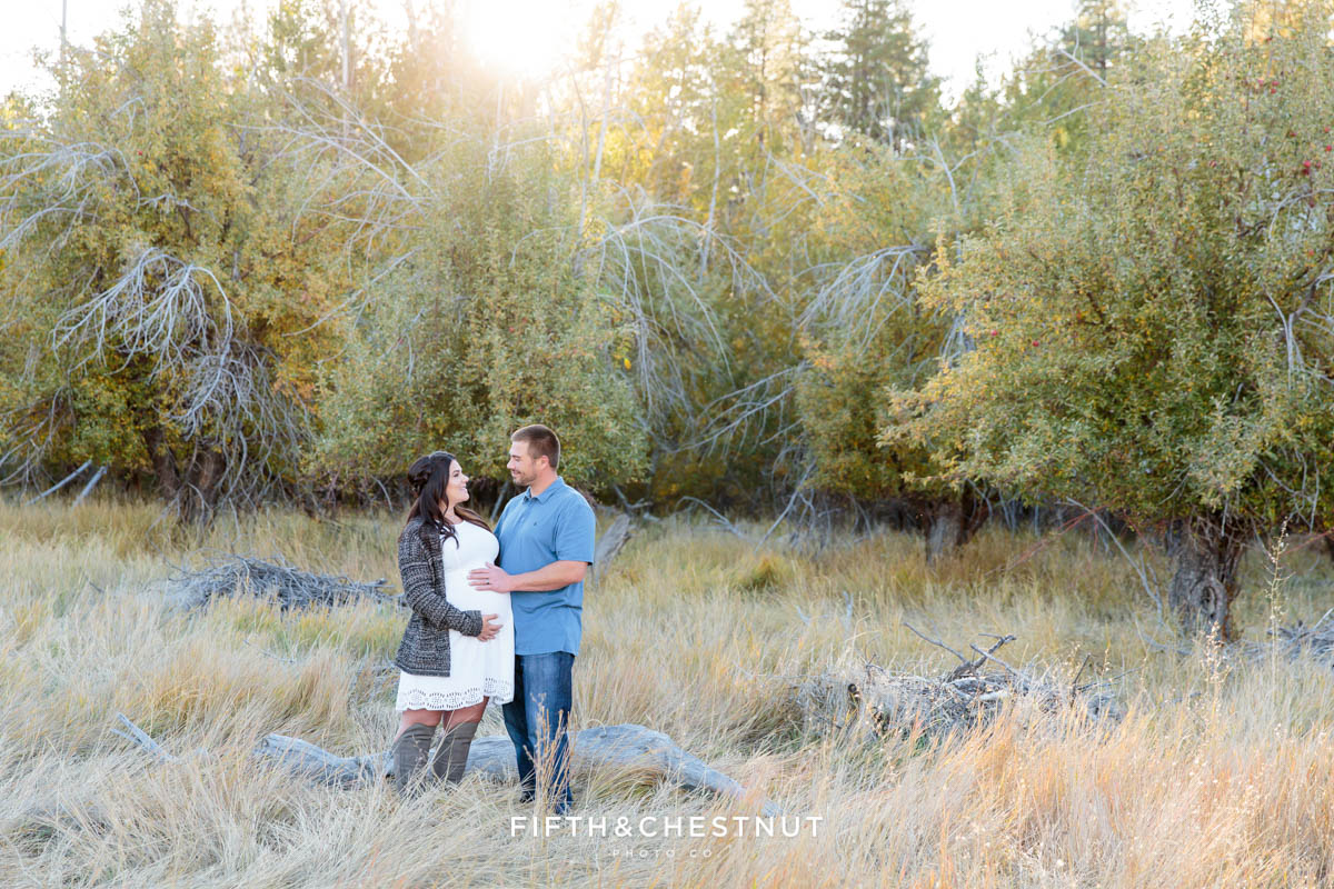 expecting couple looks at one another for their fall maternity portraits in an apple orchard field
