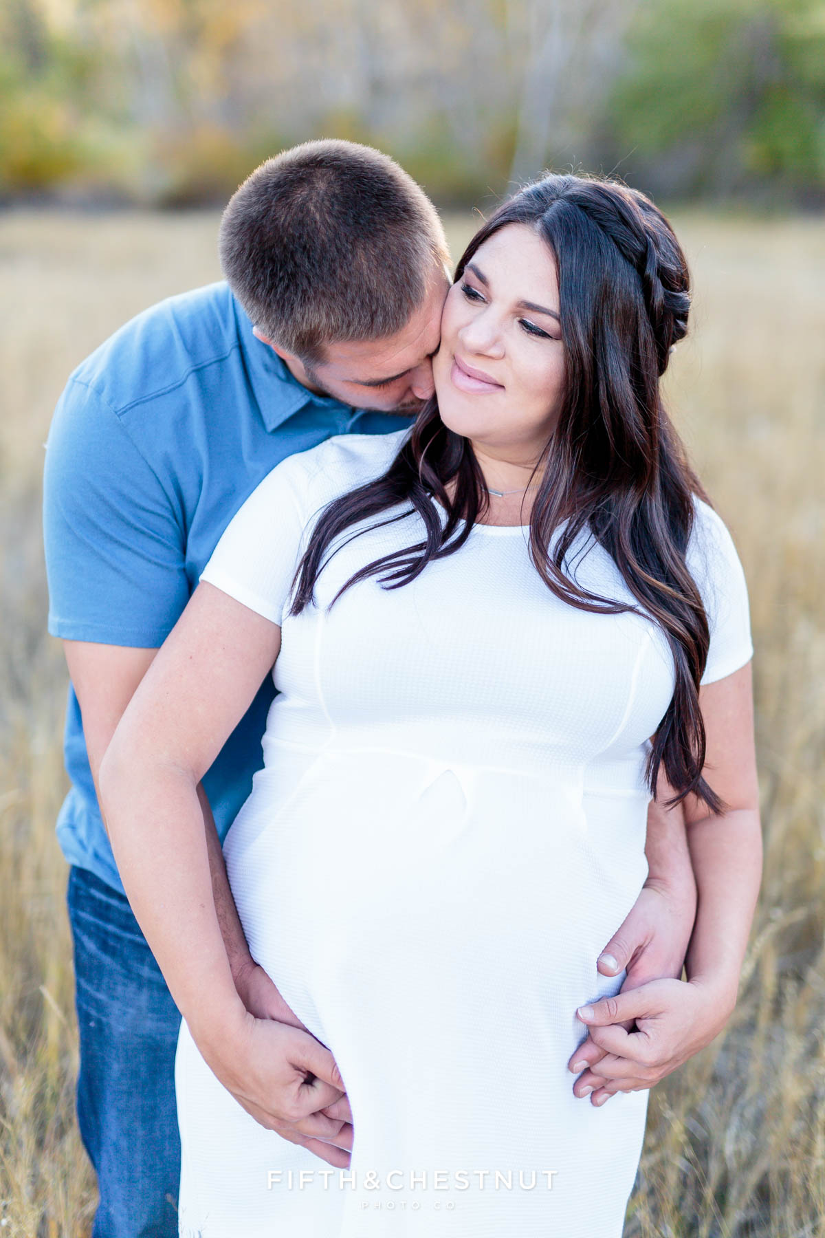 husband kisses his pregnant wife's neck as they hold hands in an open field for fall maternity portraits by Reno Maternity Photographer