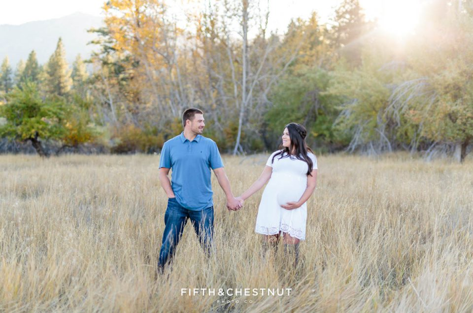 Couple stands apart and looks at each other while holding hands for their fall maternity portraits by Reno Maternity Photographer