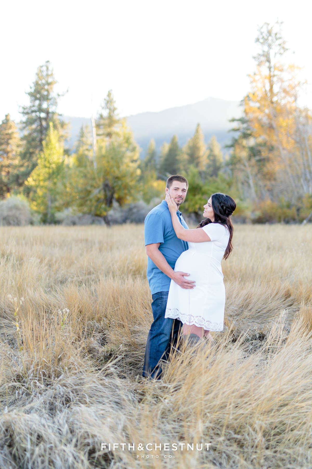 Expecting couple embrace as husband looks at camera while his wife looks lovingly towards him