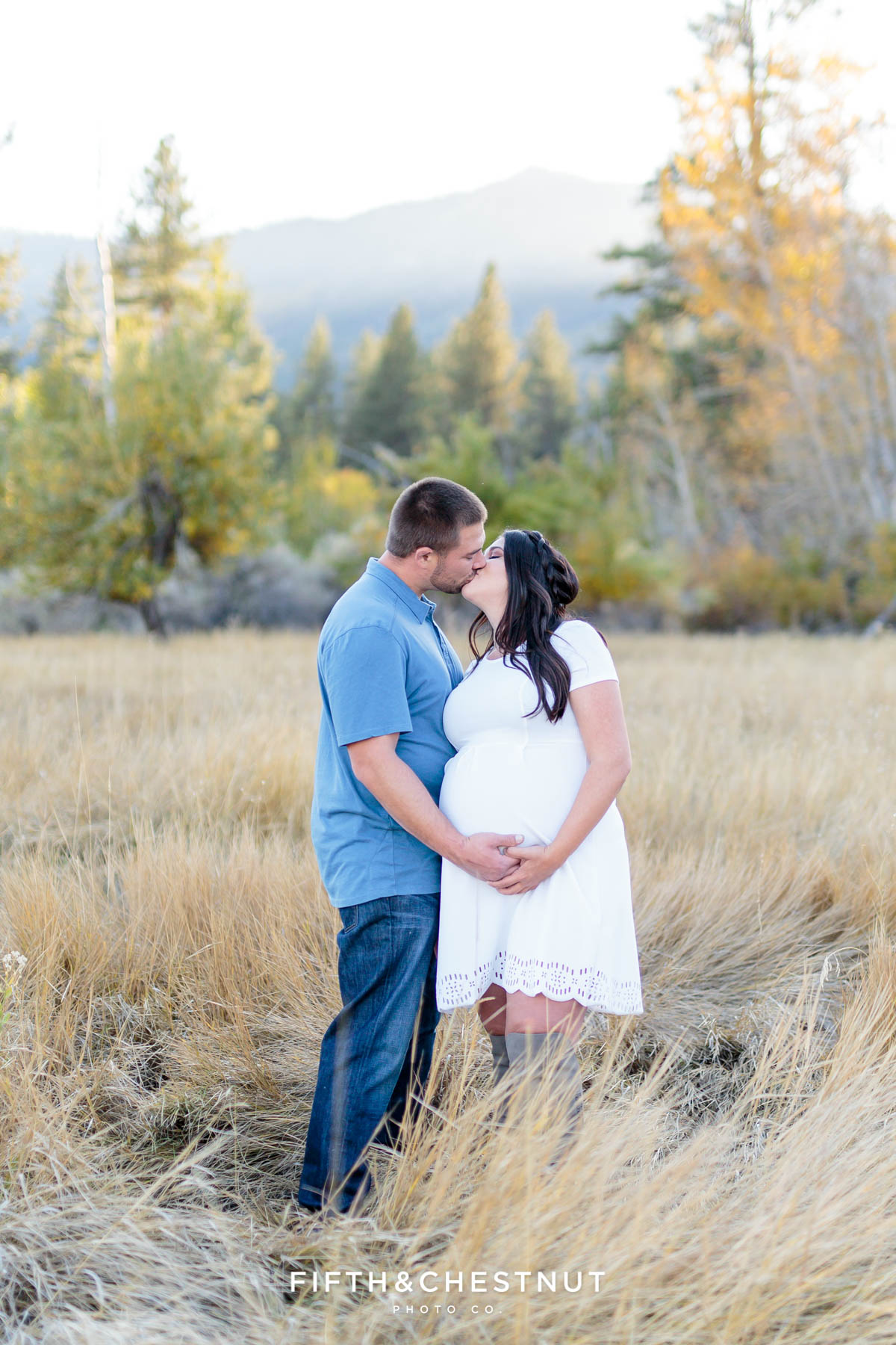 Expecting couple kiss in an open field with mountains and trees in the background for fall maternity portraits by Reno Maternity Photographer