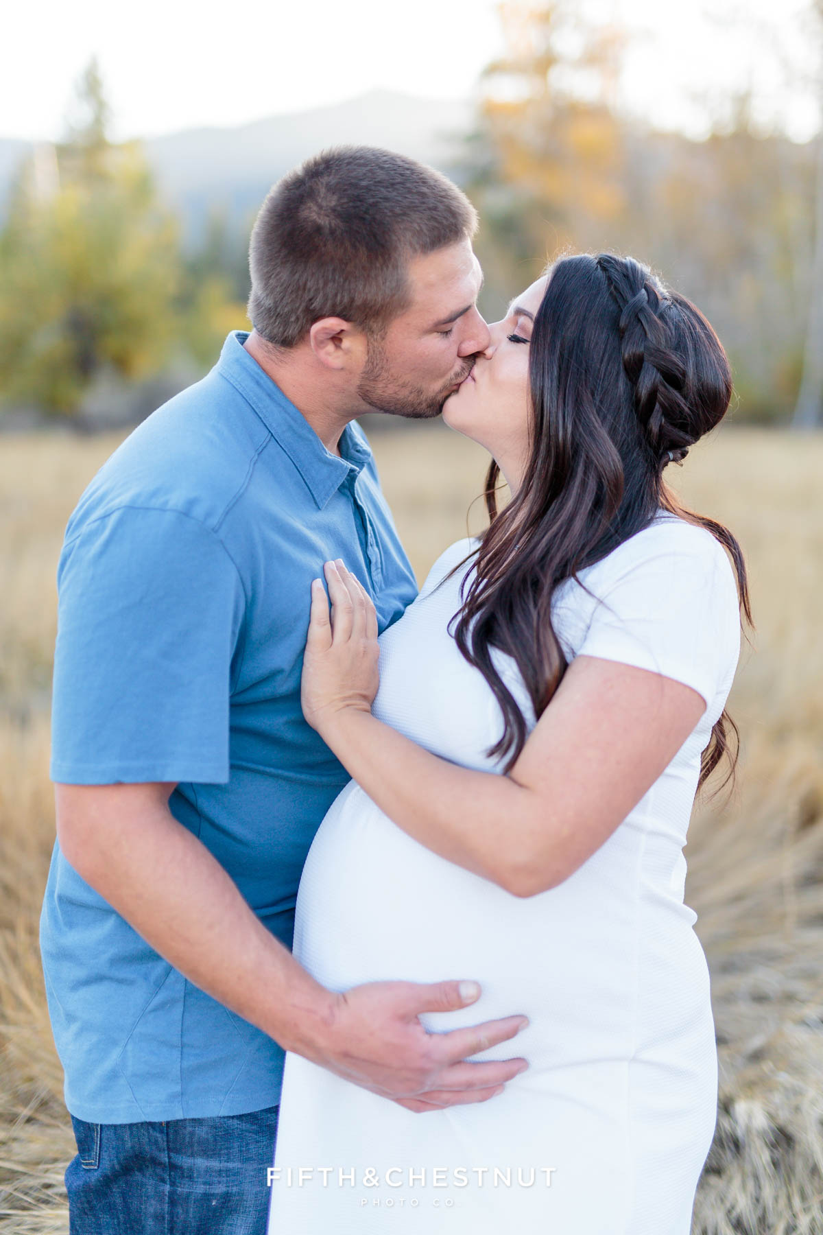 Husband and wife kiss for their fall maternity portraits by Reno Maternity Photographer in an apple orchard field with mountains behind them