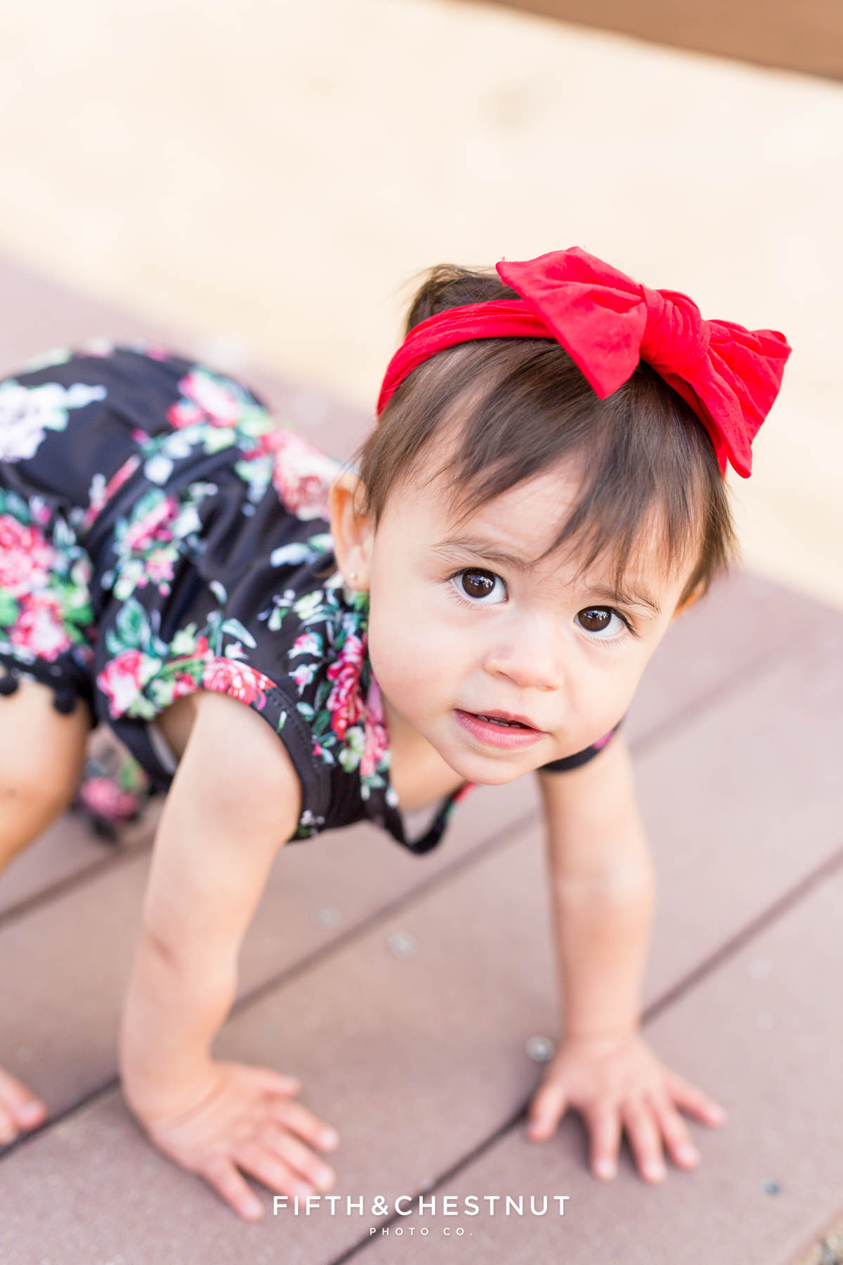 One year old girl wearing a black floral romper for her Fashionable One Year Portraits at Sand Harbor in Lake Tahoe
