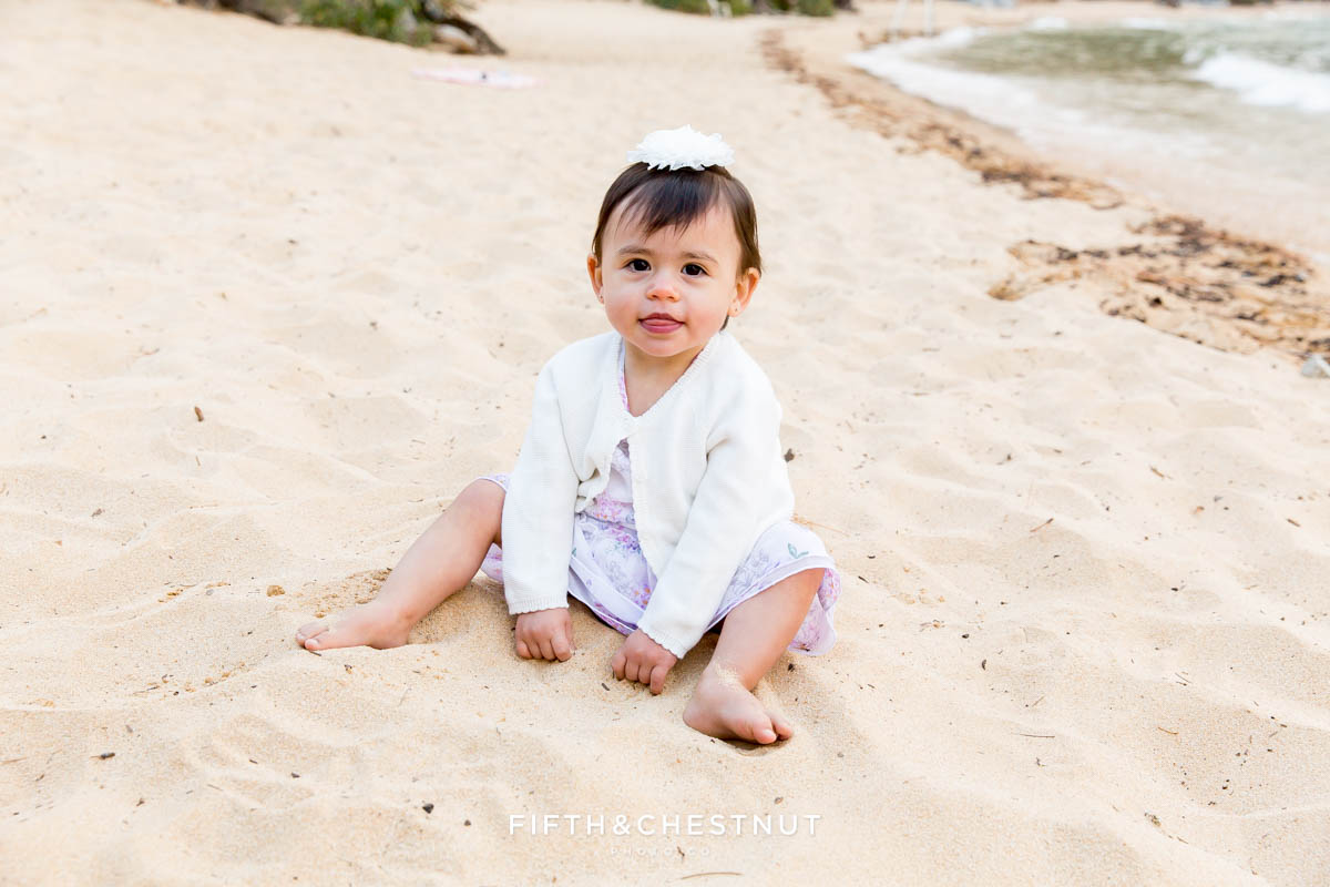 one year old girl plays in the sand wearing a light purple dress for her one year portraits by Reno Child Photographer