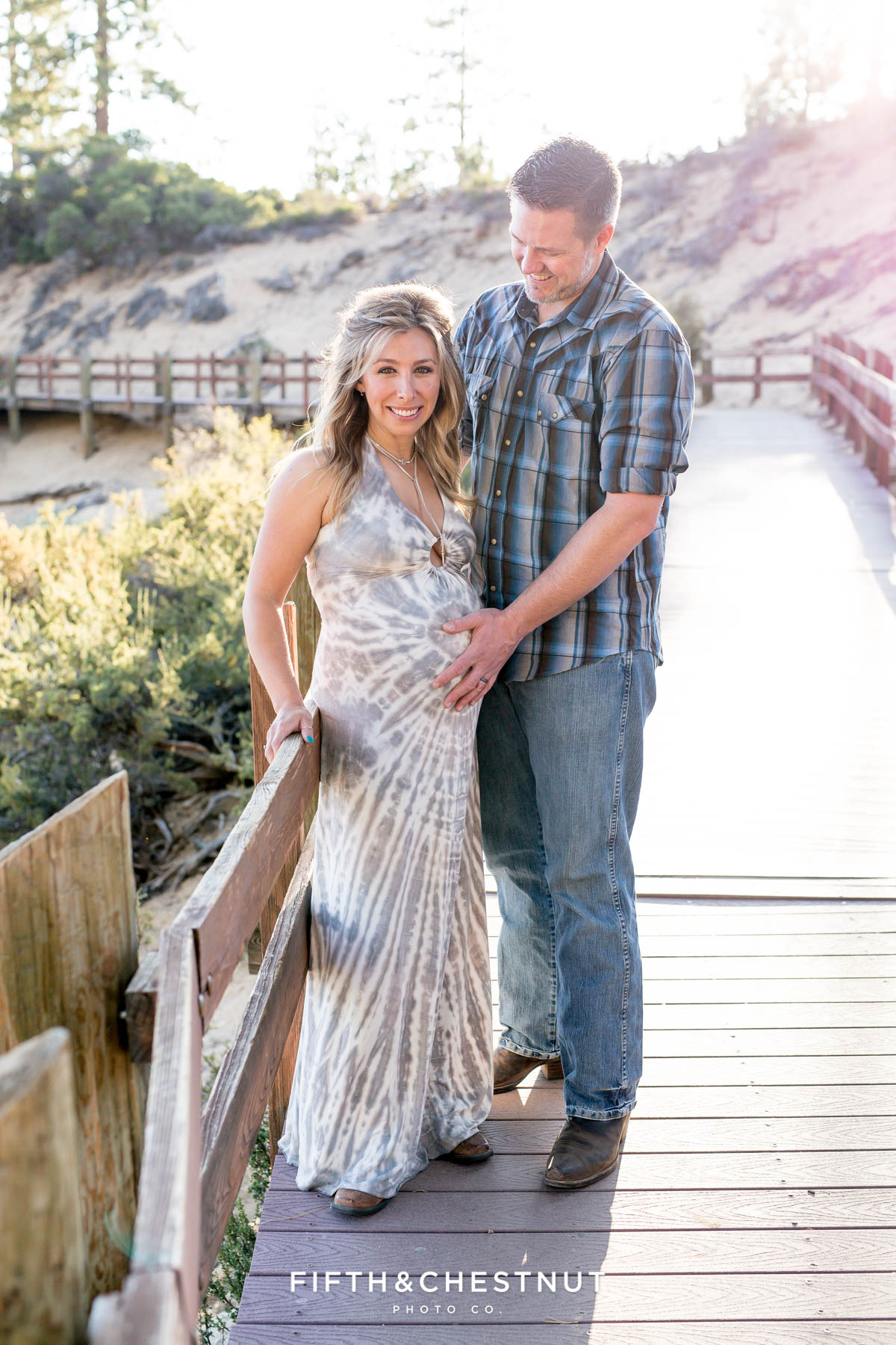 Husband holds his hand on pregnant wife's belly in Sand Harbor for their Tahoe Maternity Portraits