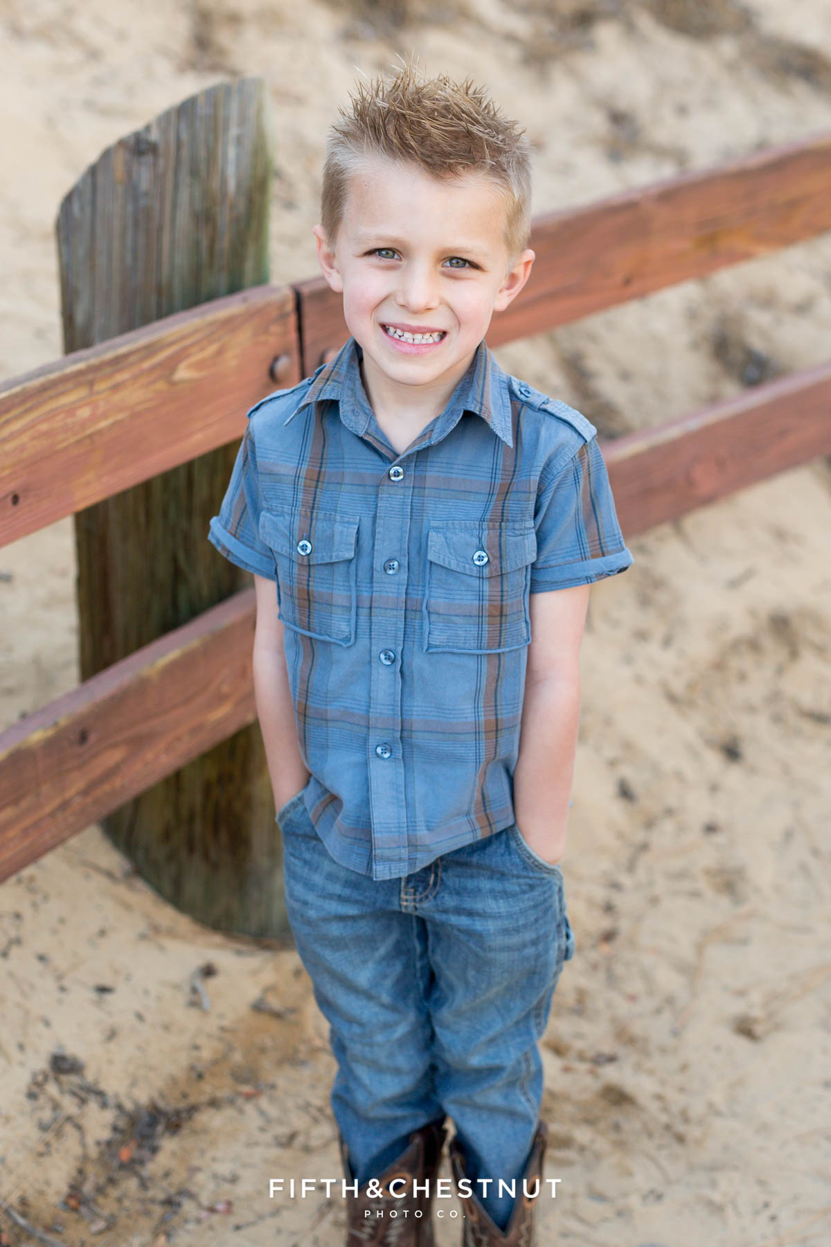 boy in plaid smiles and has hands in pockets at the sand harbor nature walk