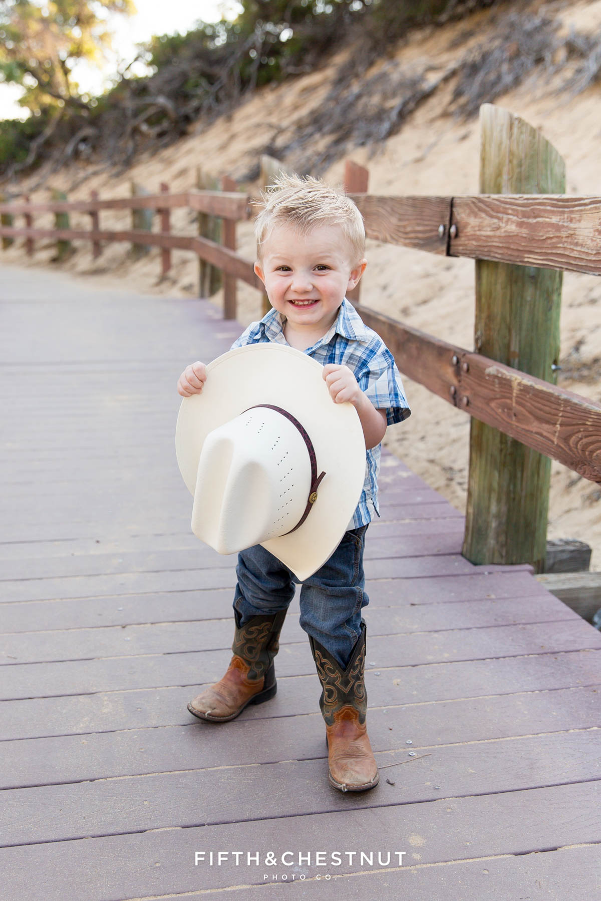 toddler holds cowboy hat wearing a plaid shirt at Sand Harbor