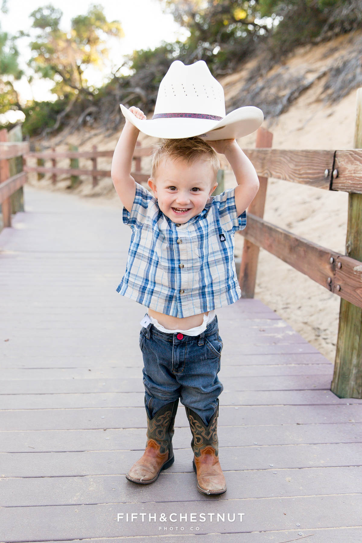 Little boy holds cowboy hat above his head while wearing cowboy boots and a plaid shirt