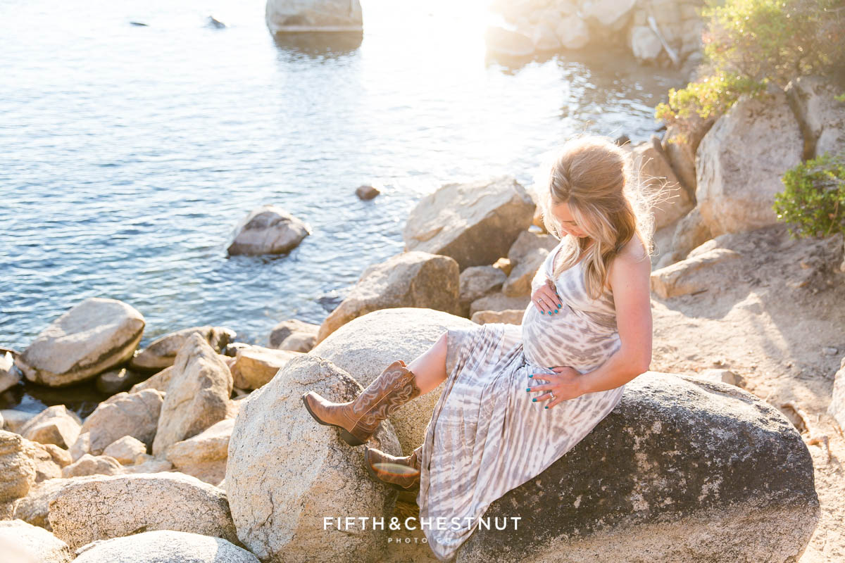 pregnant woman in a tie dye dress and cowboy boots holds her belly and looks at her bump for Tahoe Maternity Portraits