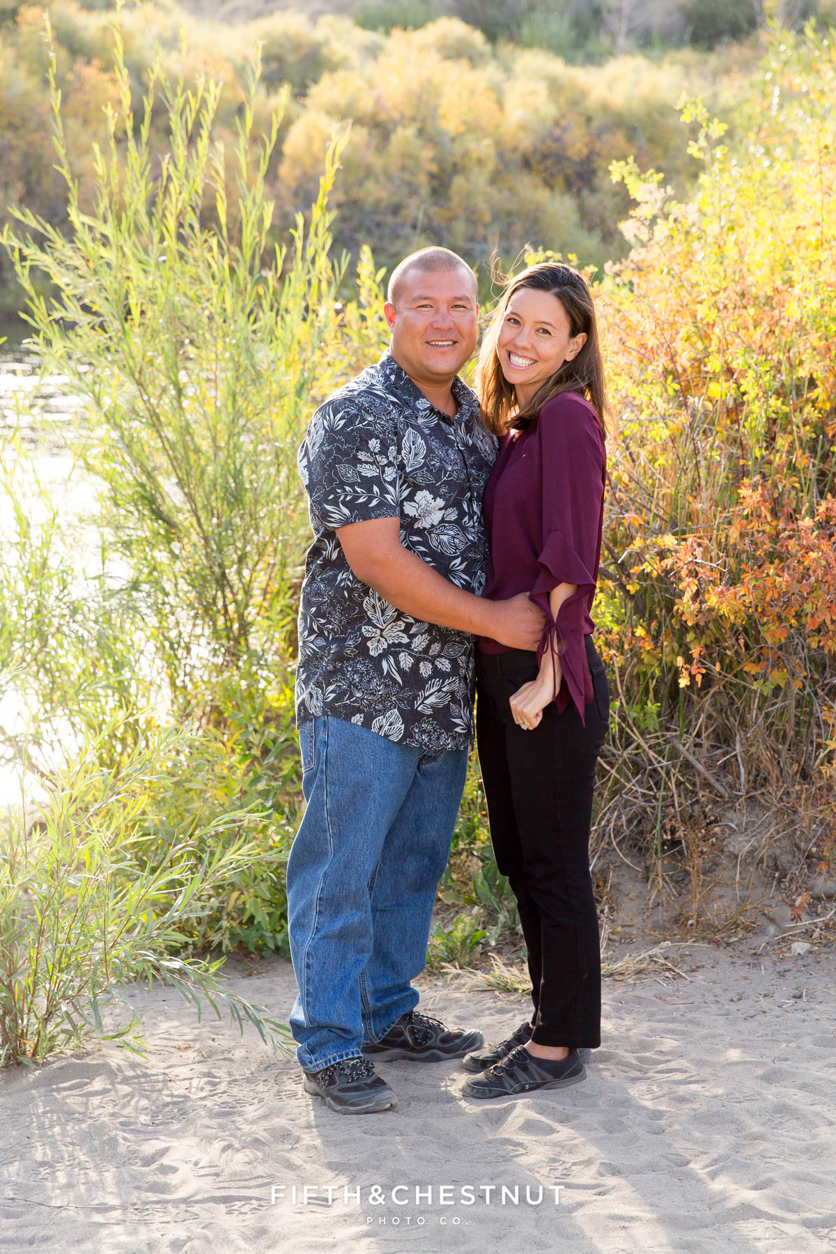 husband and wife snuggle together for vibrant fall portraits at Mayberry Park