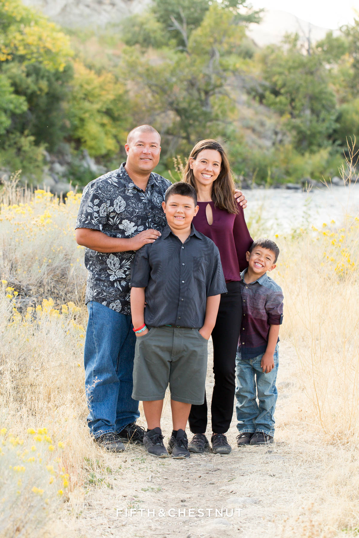 family of four stands in field with rabbitbrush for vibrant fall  portraits at Mayberry Park