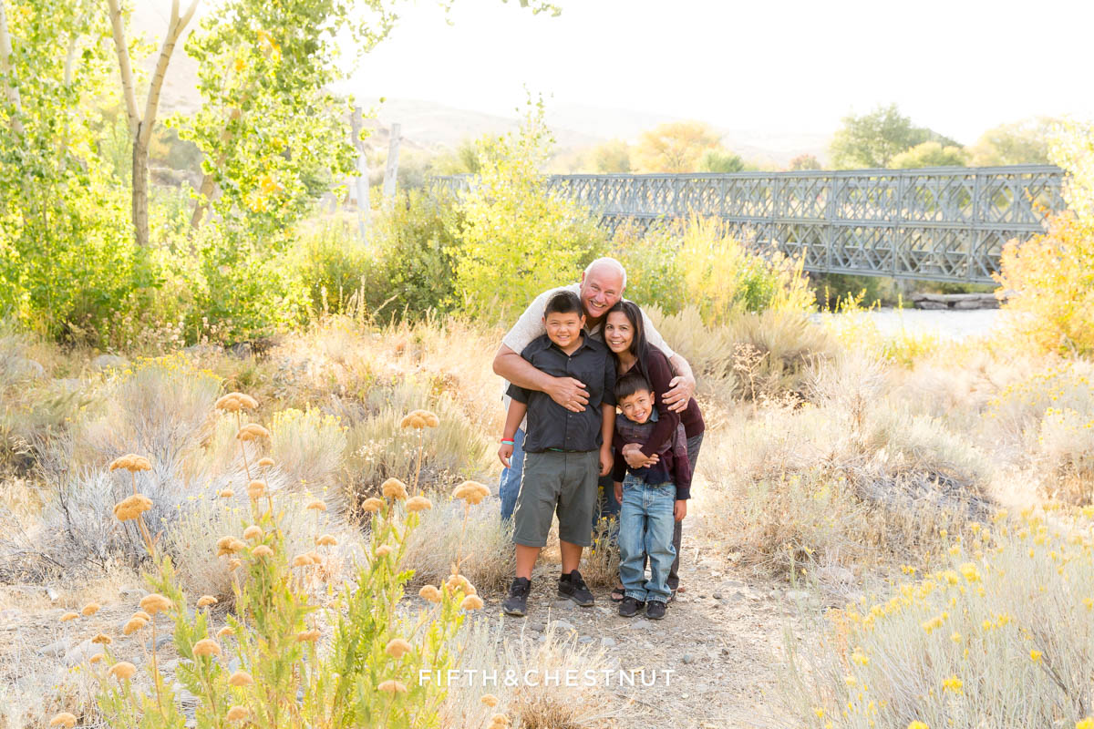 grandpa squeezes his wife and grandkids in a big bear hug for their vibrant fall portraits at Mayberry Park