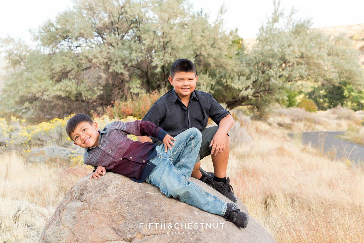 two brothers sit on a boulder for vibrant fall  portraits at Mayberry Park