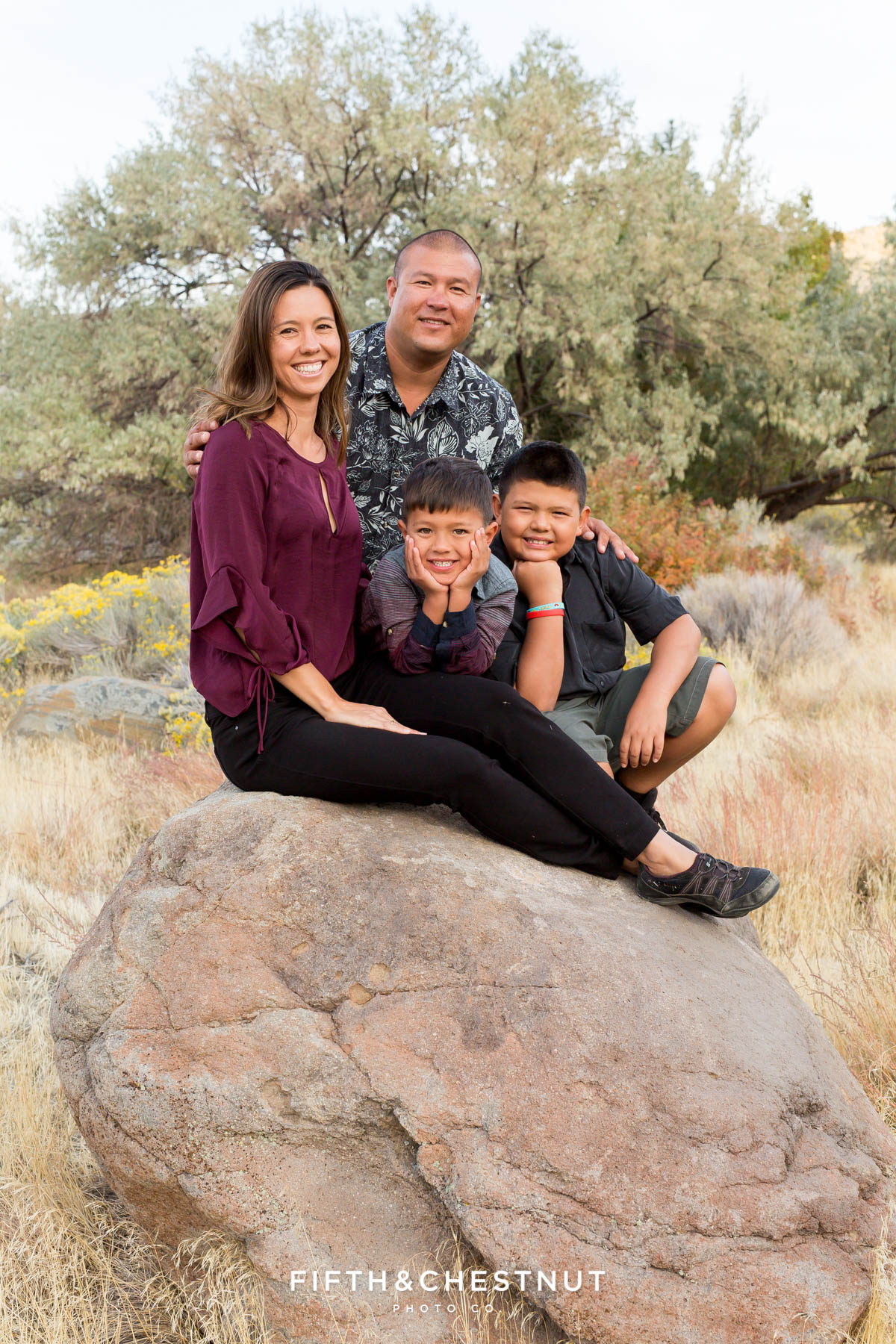 family of four visiting reno from hawaii sit on a big boulder for their vibrant fall portraits at Mayberry Park