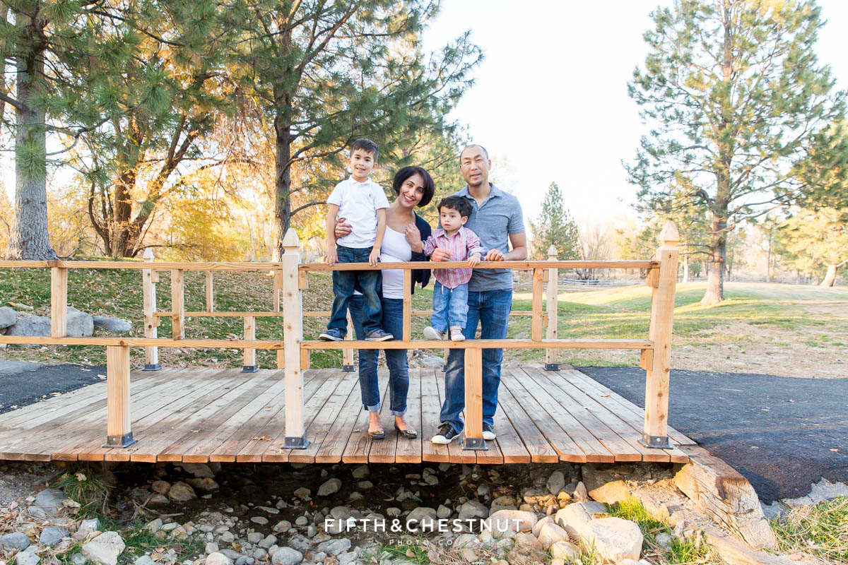 family of four stands on bridge for their Caughlin Ranch Family Portraits