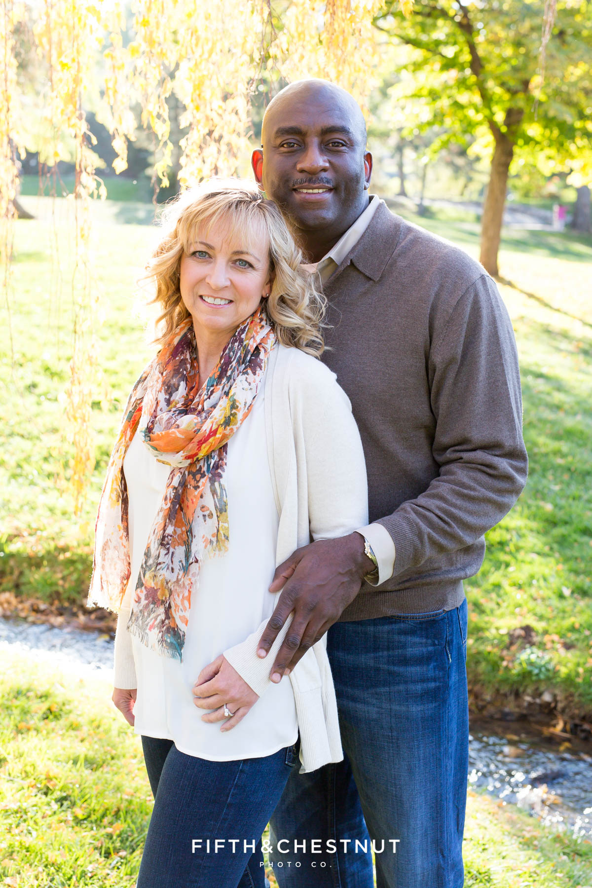 Couple dressed in fall attire embraces for their fall family portraits at Caughlin Ranch