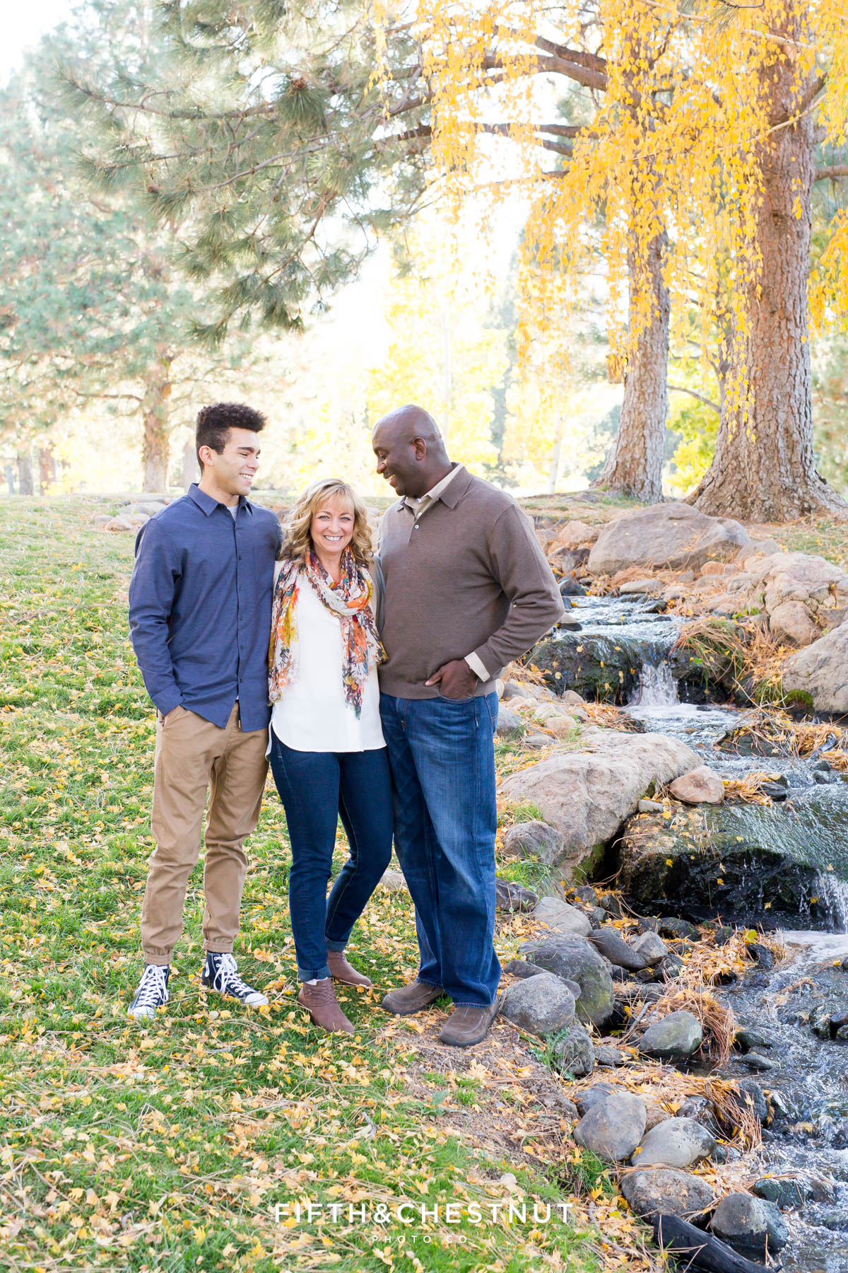 family of three stand by creek and laugh during their fall family portraits at Caughlin Ranchfall family portraits at Caughlin Ranch by Reno Family Photographer