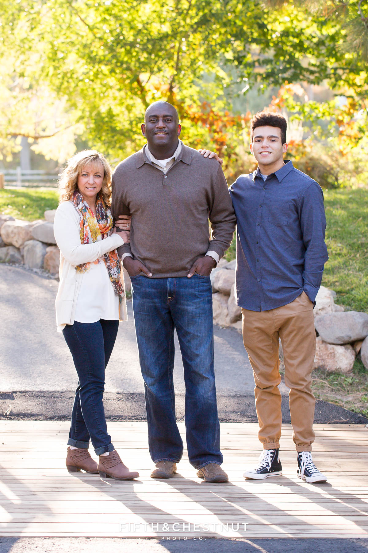 Family of three stands on a bridge during their fall family portraits at Caughlin Ranch by Reno Family Photographer
