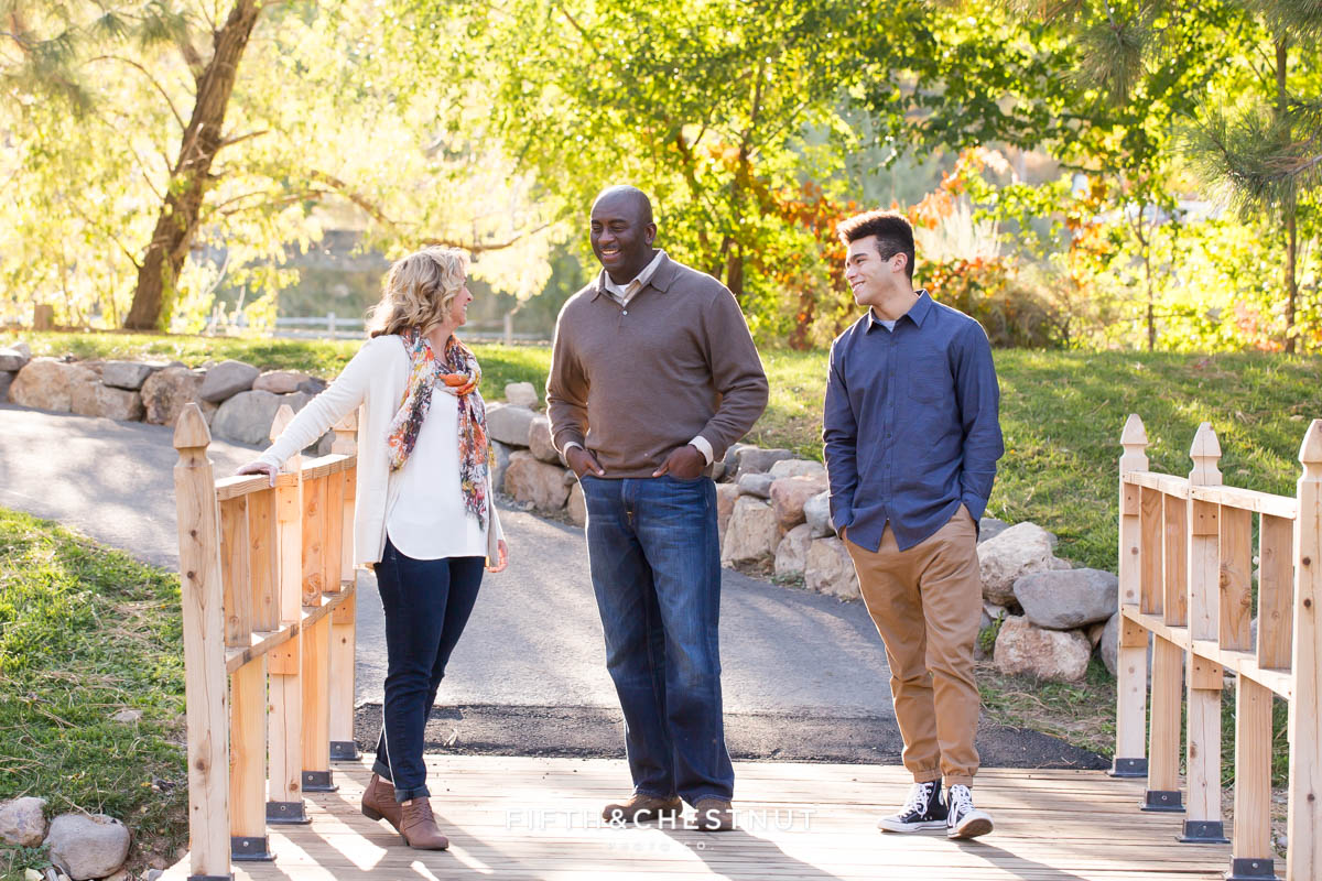Family of three in fall clothing laugh with one another for their fall family portraits at Caughlin Ranch
