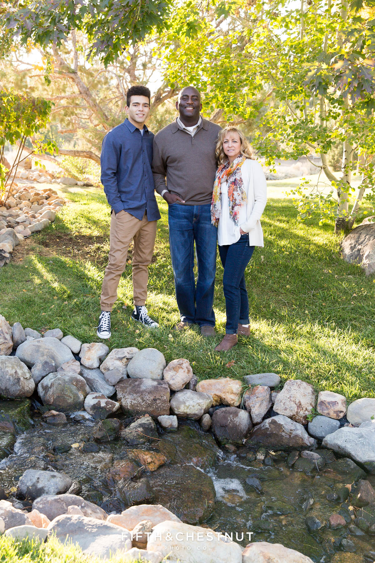family of three stand near creak and simile for their fall family portraits in Reno