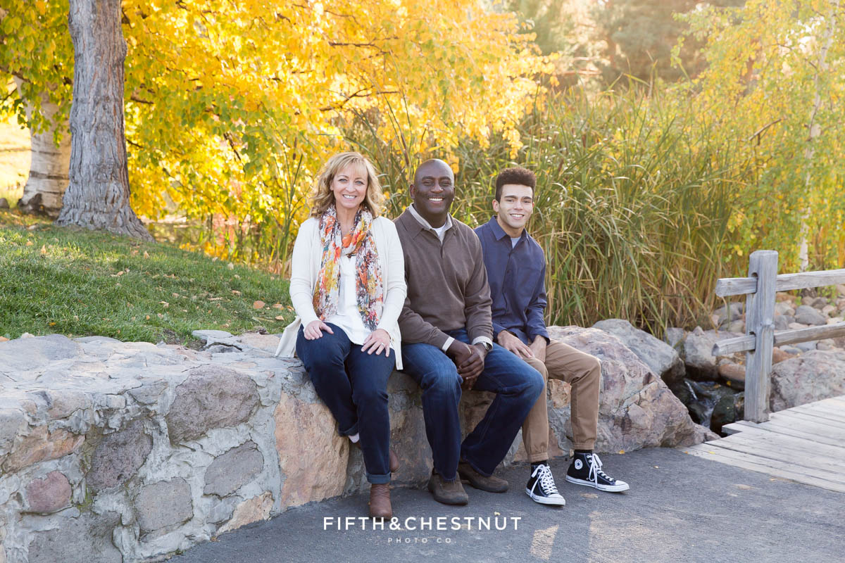 family of three sit on rocks at caughlin ranch for portraits
