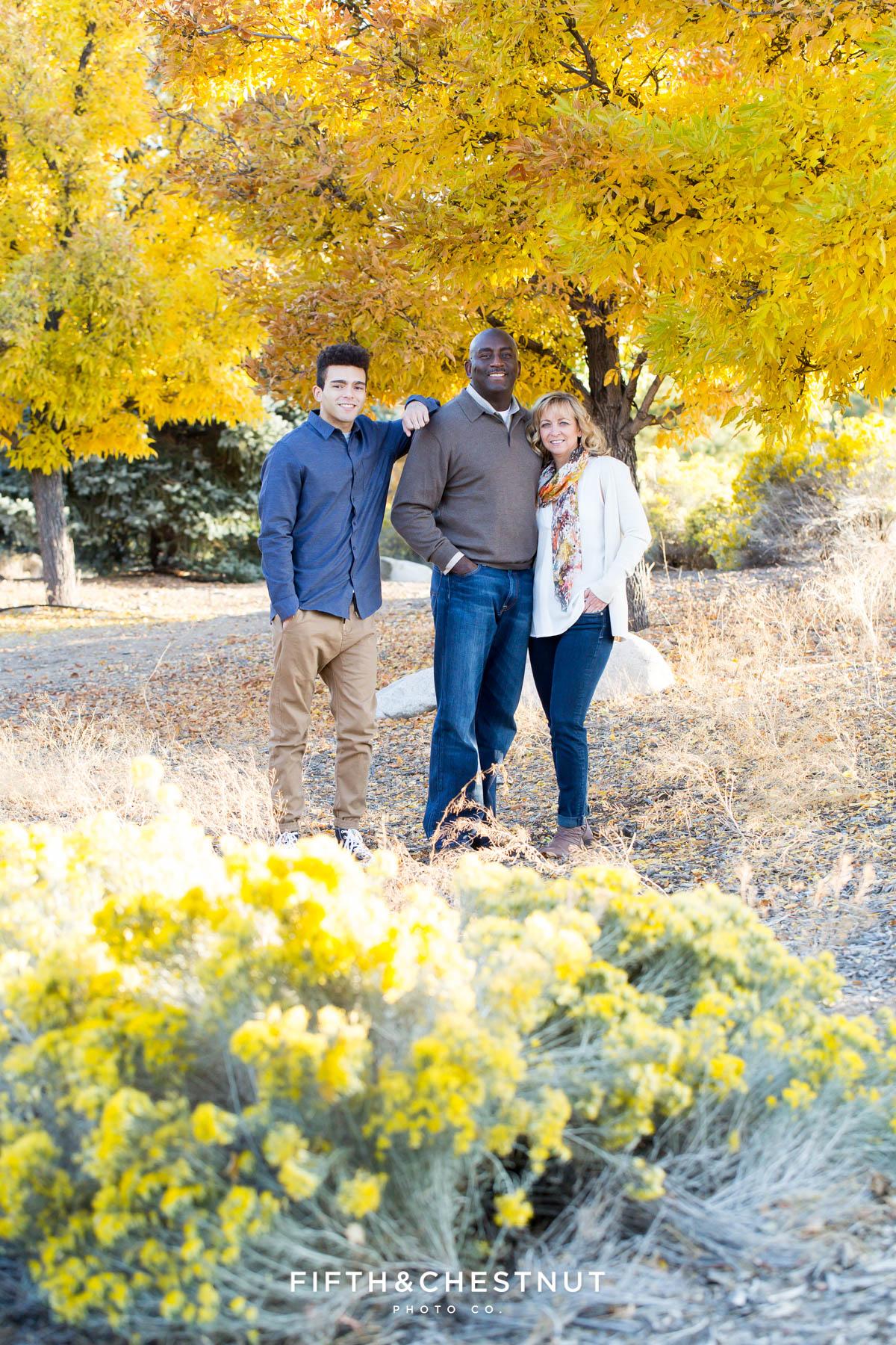 Family of three stands near bright yellow tree for Reno fall family portraits