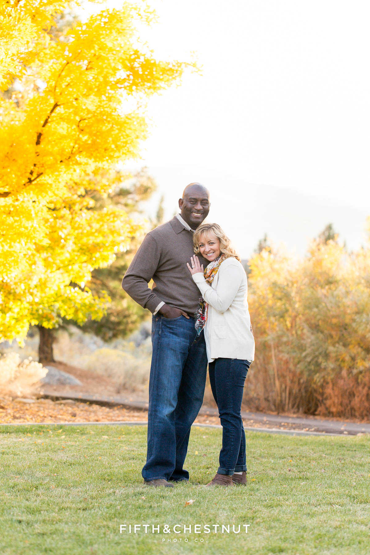 couple snuggles during Reno fall family portraits