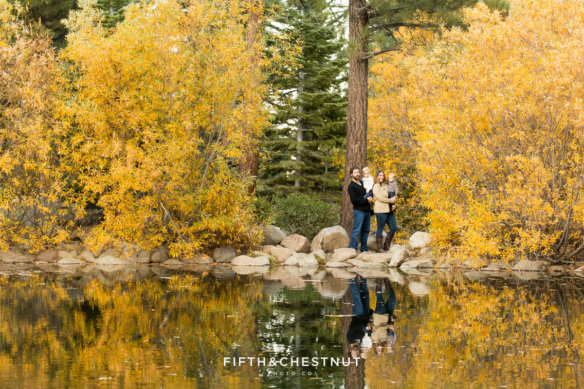 Family of four standing near pond showing their reflection among yellow trees for their Fall Galena Creek Portraits