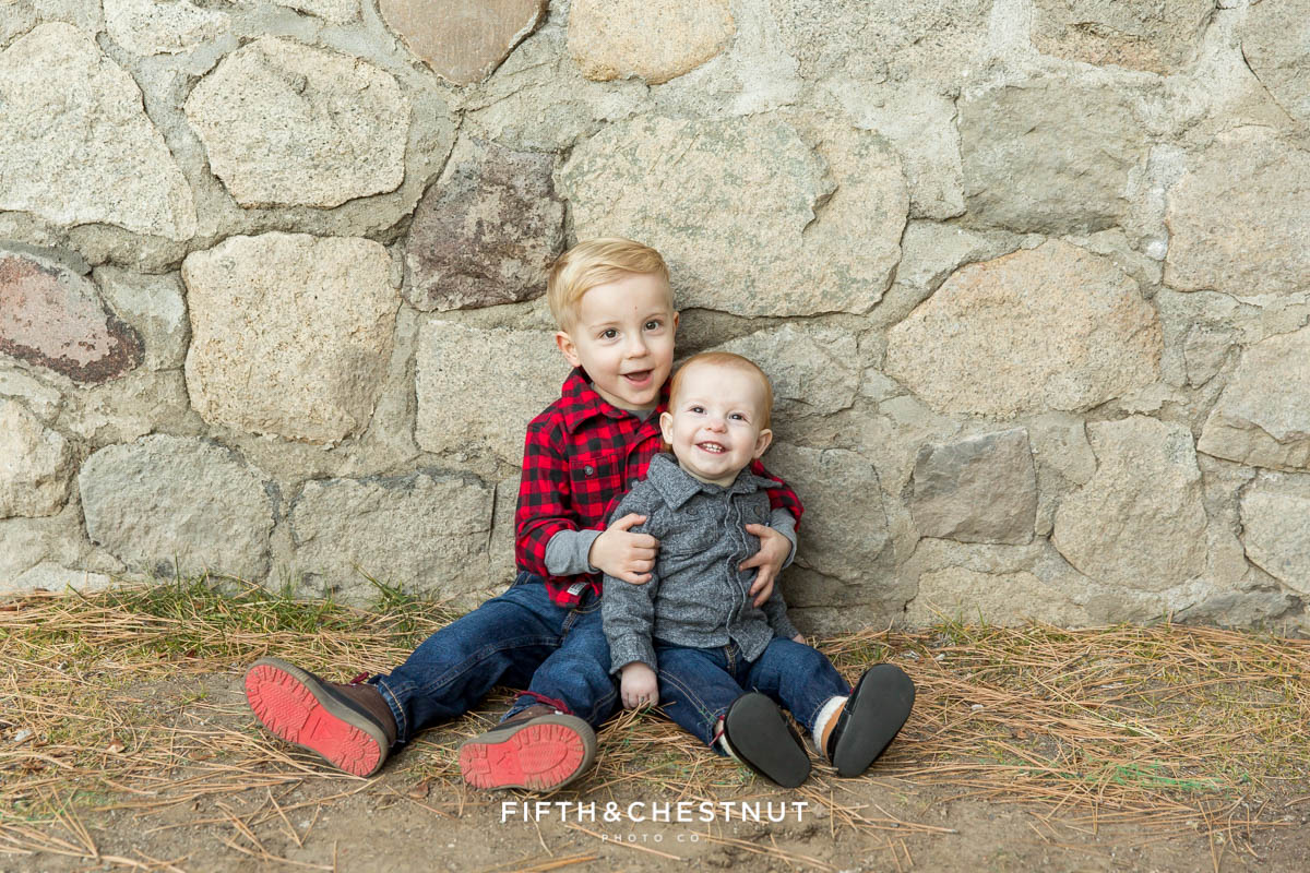 young brothers sit together against a stone wall for their reno family photos at galena creek park