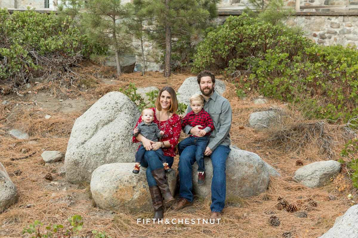 Family sitting together on rocks below the Galena Creek Fish Hatchery for their fall family photos at galena creek park