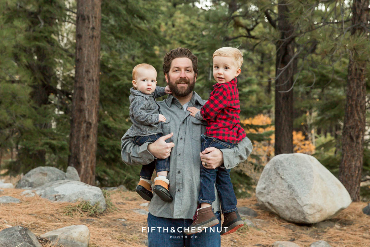 Portrait of father and sons with pine trees in the background