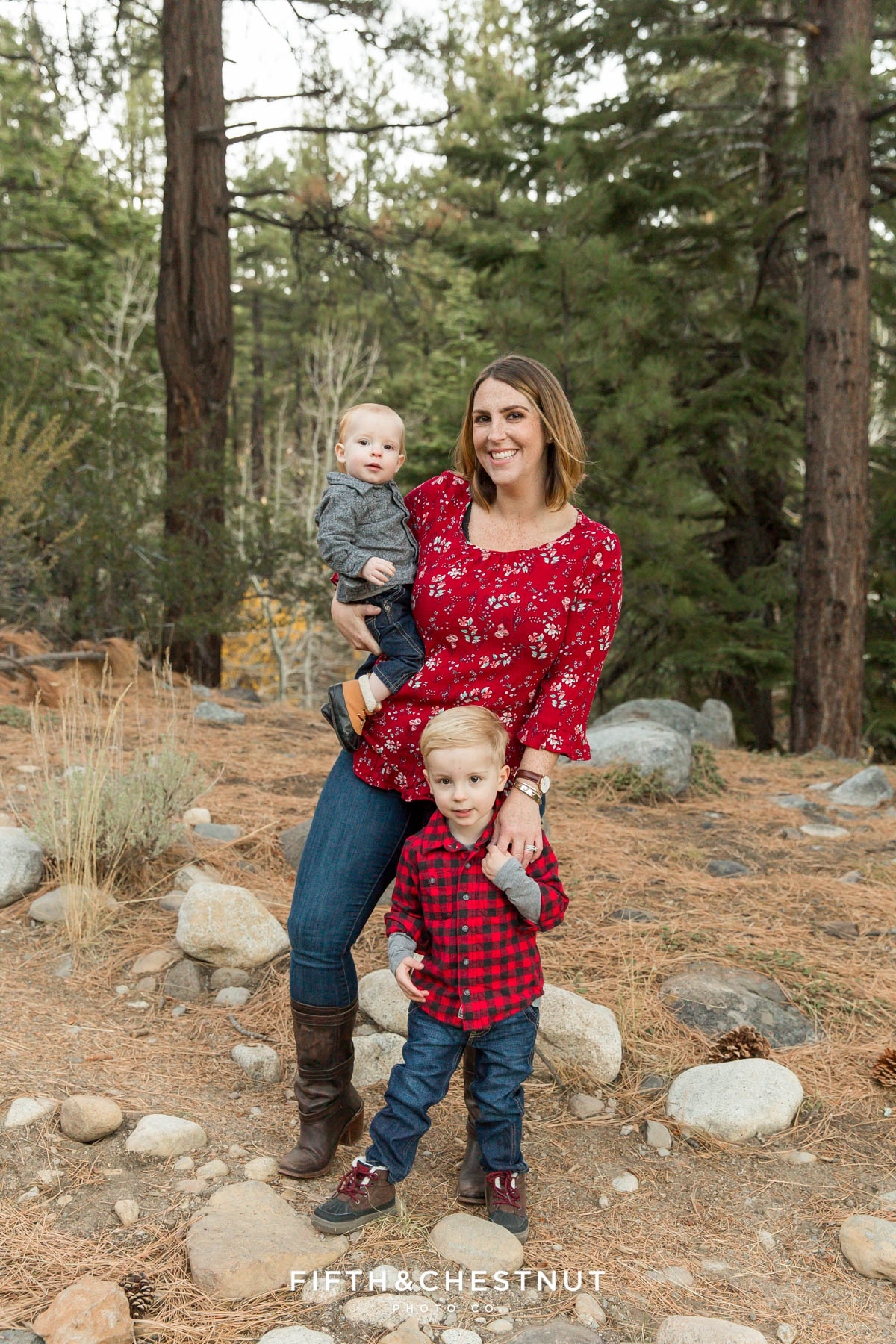 portrait of mother and sons with pine trees and rocks in the background