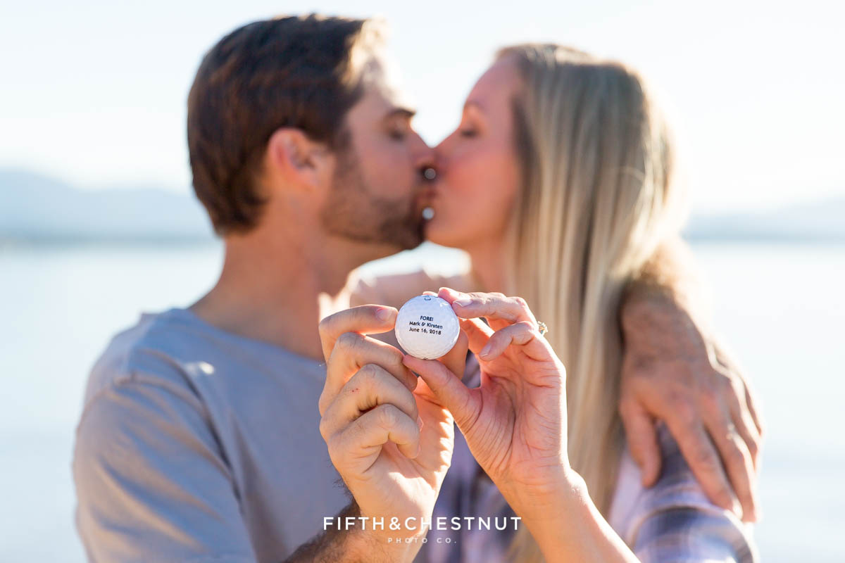 Engaged couple shows off their golf ball wedding favor for their fall Nevada Beach engagement