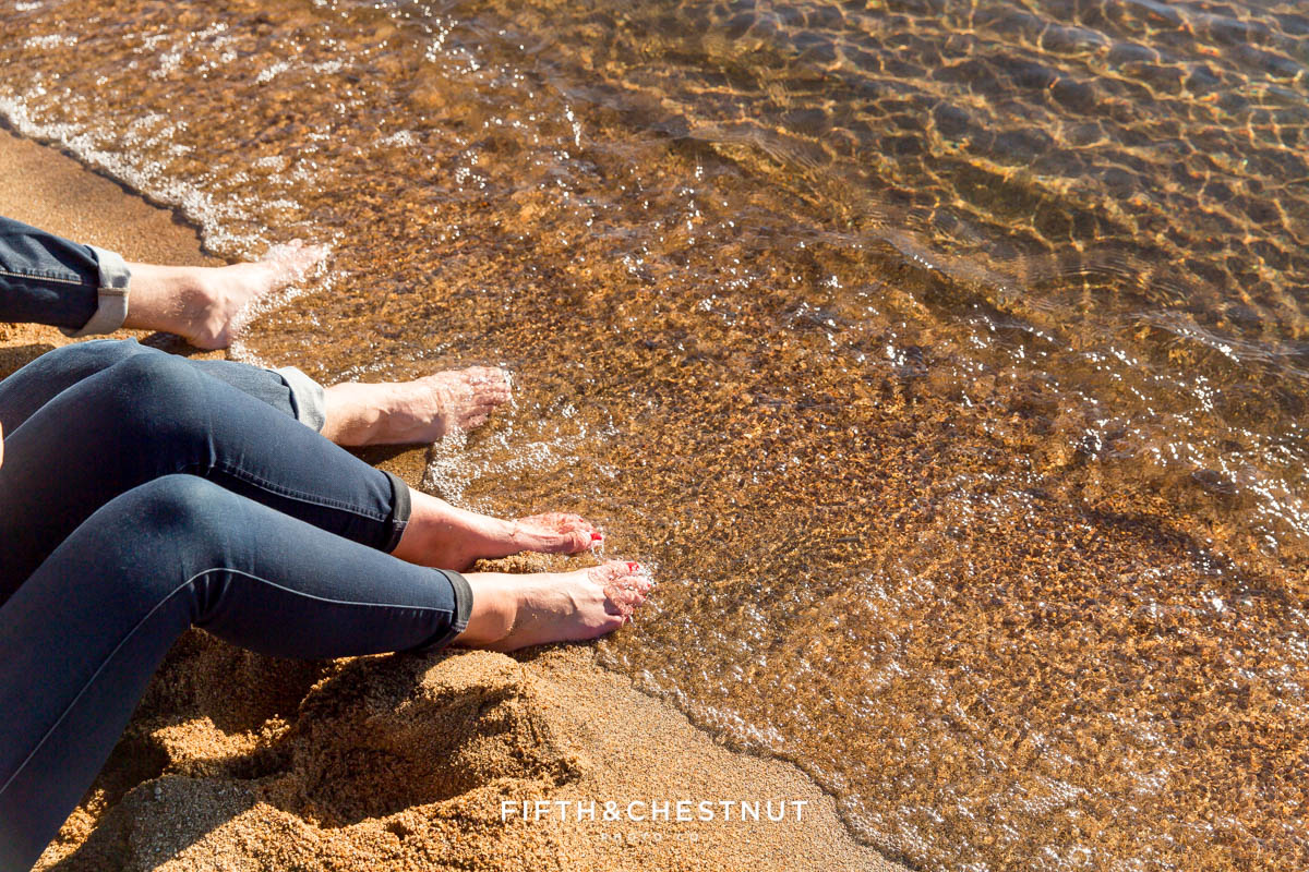 engaged couple stick their feet in lake tahoe for their fall Nevada Beach engagement