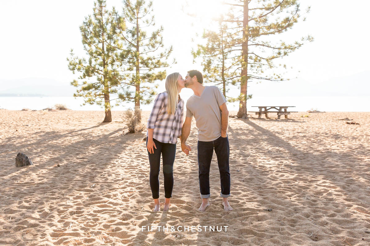 engaged couple kiss on nevada beach for engagement portraits with Lake Tahoe wedding photographer