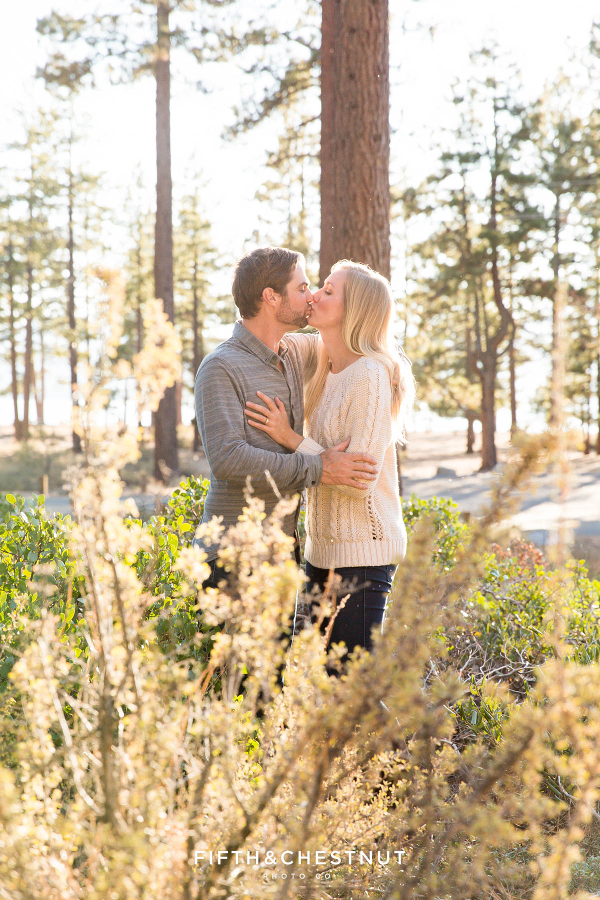 couple kisses among pine trees and manzanita for their fall Nevada Beach engagement