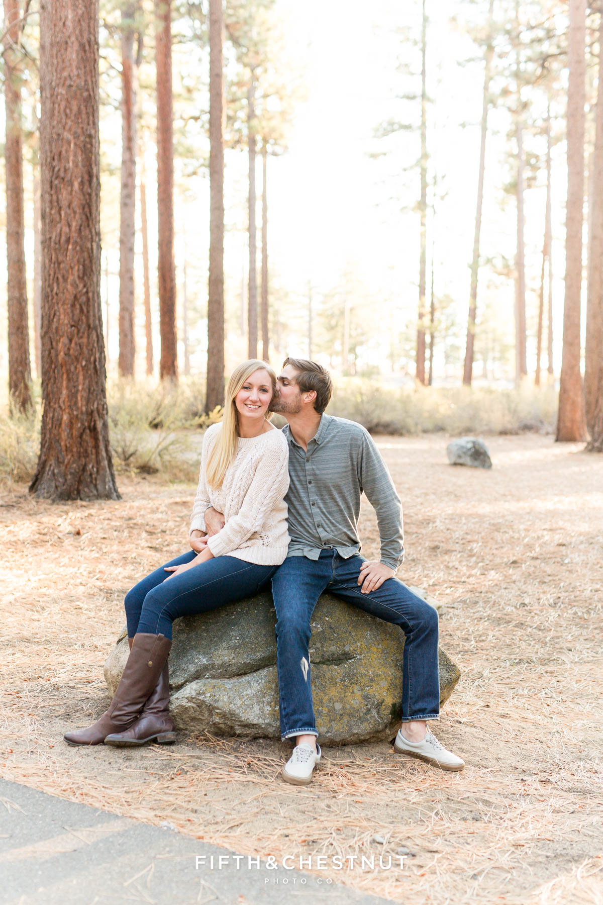 engaged couple sits on a rock at Nevada Beach for their Lake Tahoe engagement portraits