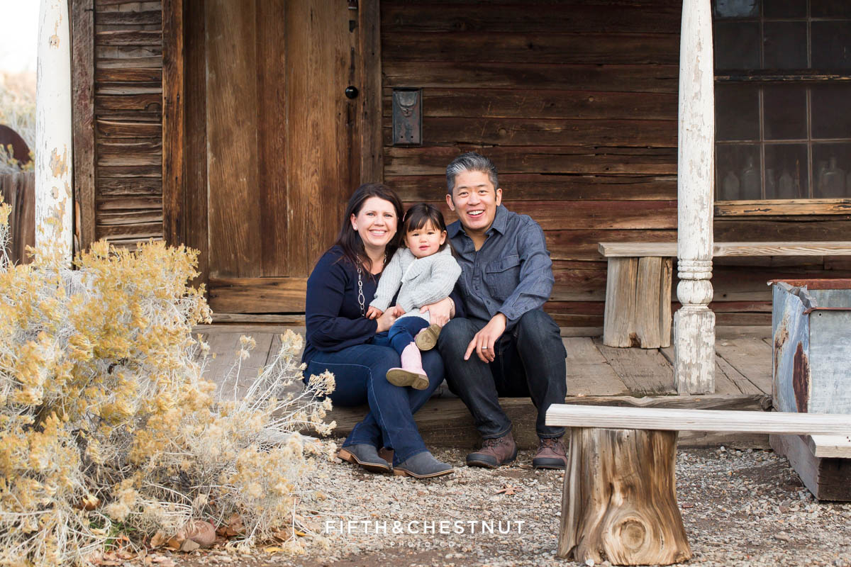 family of three sits on wooden porch for their Adorable Reno Family Portraits