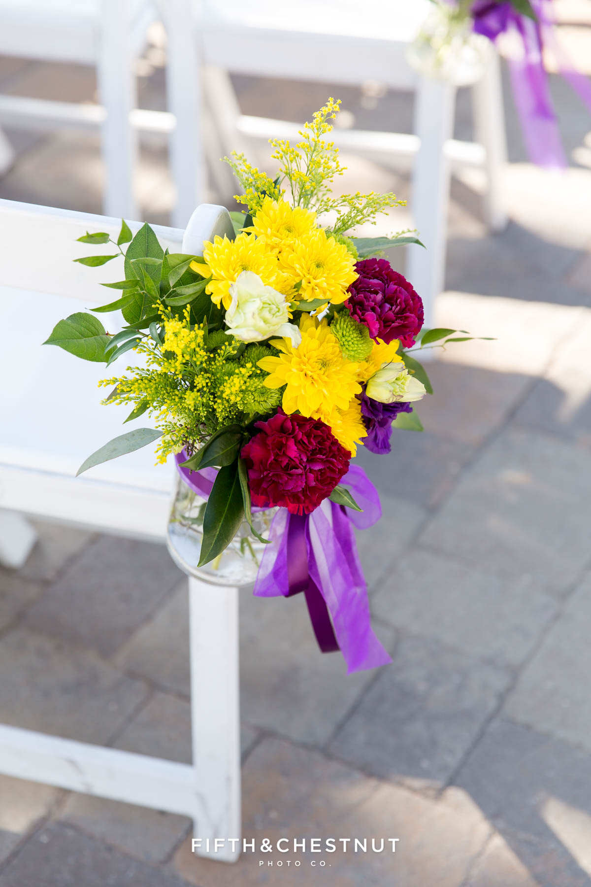 bright yellow and purple fall ceremony chair flowers by Serendipity florist for a Bright fall wedding at the Grove by Reno Wedding Photographer