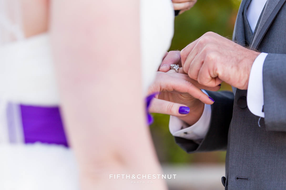 Groom putting his bride's ring on during a Bright fall wedding at the Grove by Reno Wedding Photographer