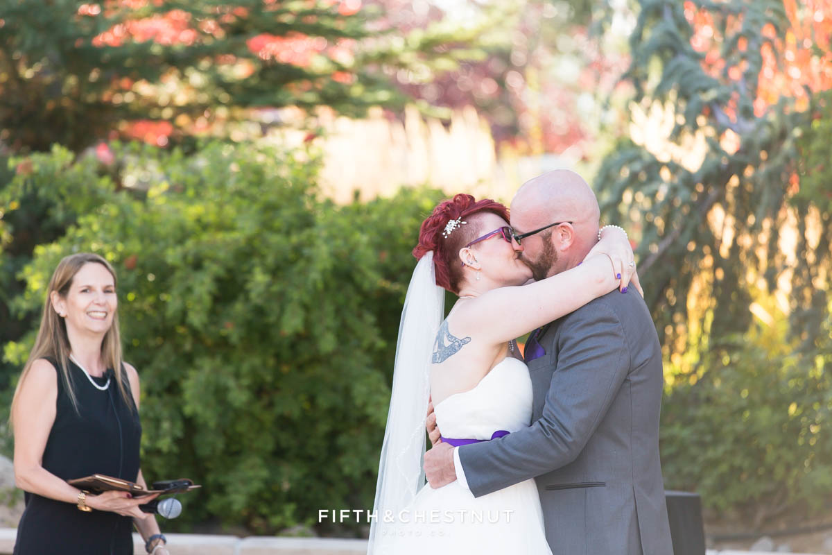bride and groom kiss as husband and wife during their Bright fall wedding at the Grove by Reno Wedding Photographer